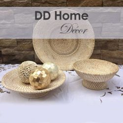 lovely table setting showing stylish chic woven bowls and a woven plate with mother of pearl decorative balls on a crocheted tablecloth with a brick wall in the background