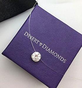 floating illusion wire diamond pendant placed on purple desert diamonds jewelry box